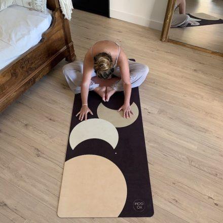 Mathilde Corbin médite sur son tapis de yoga Performance Yogom couleur bleu nuit aubergine avec motifs lunes colorées