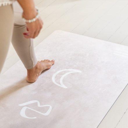 Femme qui pratique le yoga sur son tapis Yogom Rituel gris