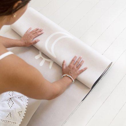 Femme qui plie le tapis de yoga Rituel gris perle pour le ranger