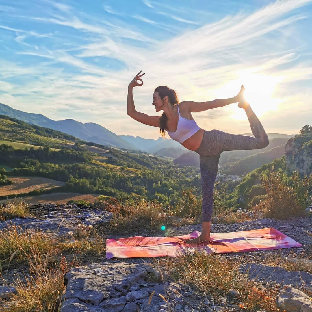 Femme qui fait du yoga en pleine nature sur son Tapis de Yoga Voyage Yogom