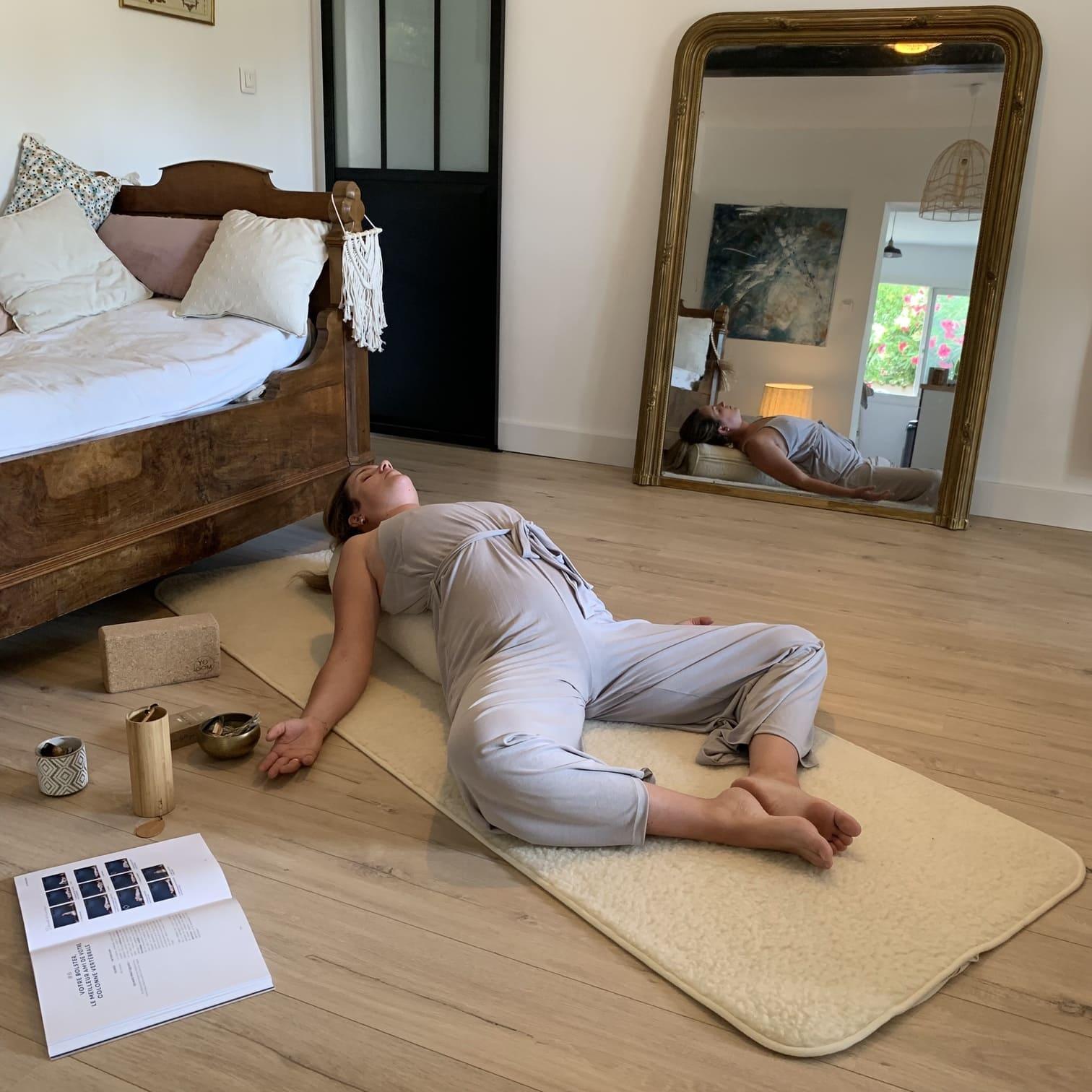 Femme qui fait du Yin Yoga sur son bolster et son tapis en laine