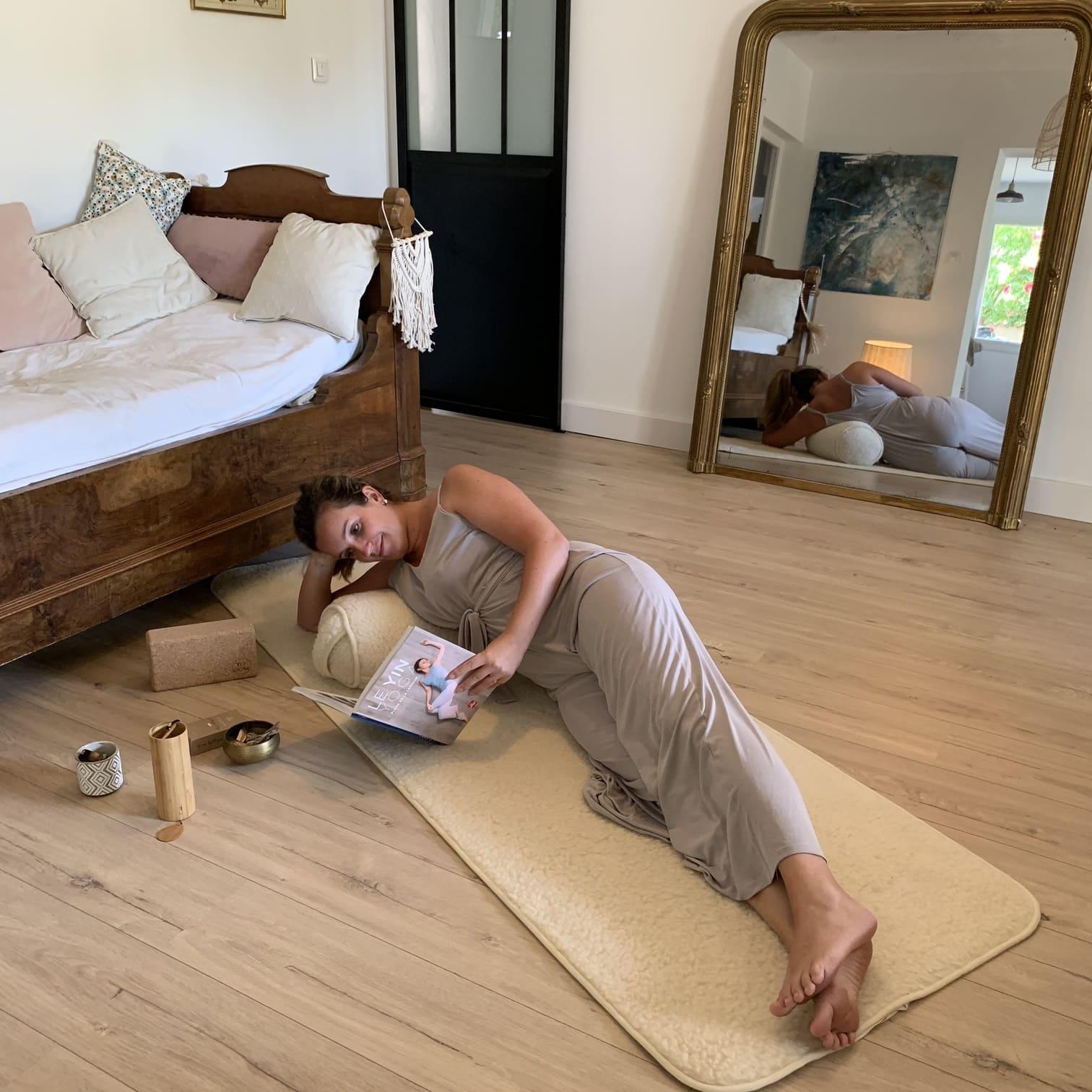 Femme qui lit allongée sur son bolster de yoga en laine
