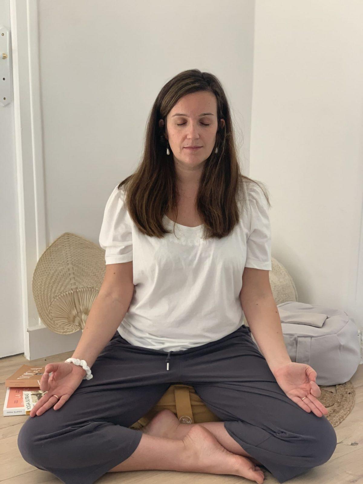 Femme qui médite en position du lotus sur son bolster