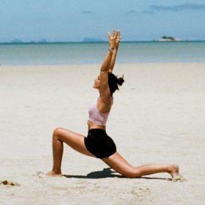 Laura de Yog it Simple qui fait une fente genou au sol sur la plage