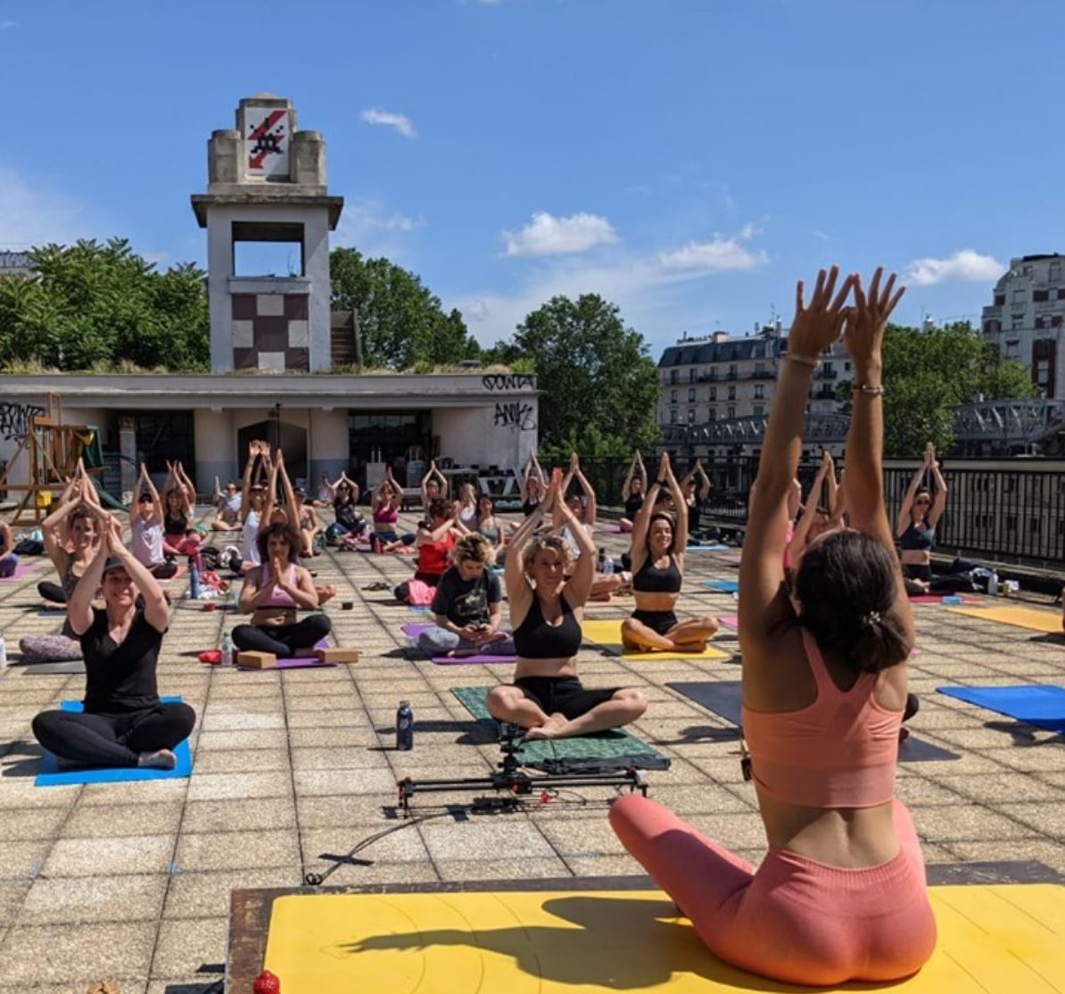 Jeune femme qui donne un cours collectif de yoga sur les toits de paris