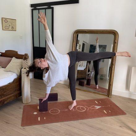 yogini réalise la posture du guerrier sur le côté en appui sur un bloc yogom