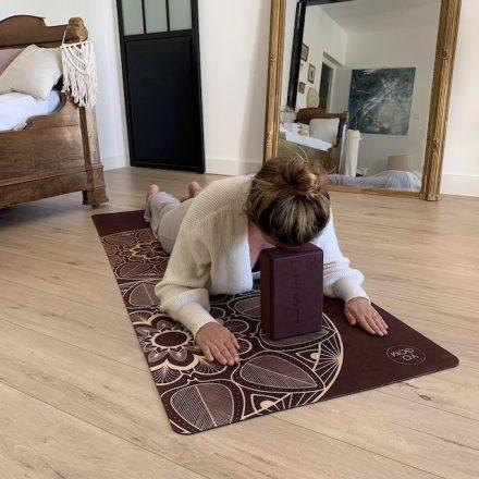 jeune femme allongée sur le ventre au sol sur un tapis de yoga performance bordeaux mandala en posture du corbeau avec la tête posée sur un bloc yoga