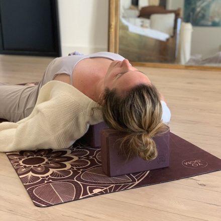jeune femme allongée sur un tapis de yoga yogom avec deux briques en eva bordeaux sous la tête